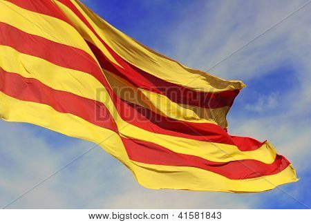 Waving Flag Of The Catalunya (catalonia) On Background Of The Blue Sky.