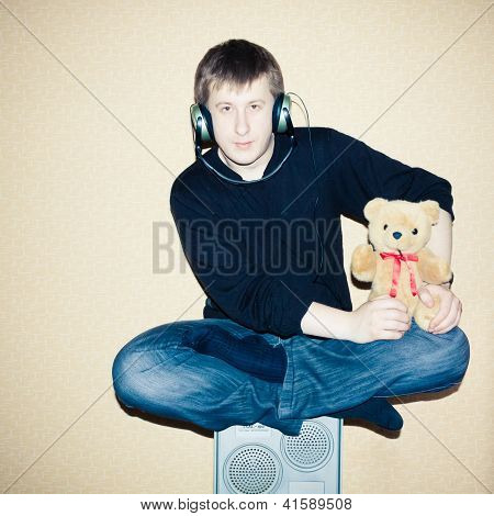 Portrait Of A Relaxed Young Guy Sitting On Subwoofer