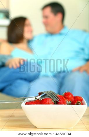 Closeup Bowl Of Strawberry With Two Fork And Couple On Backgroun