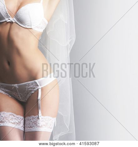 Young sexy bride in erotic lingerie over grey background