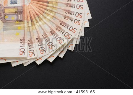A lot of european money over black background