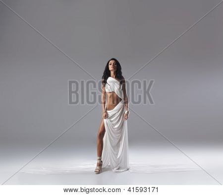 Aphrodite styled young woman over grey background with a lot of blank space