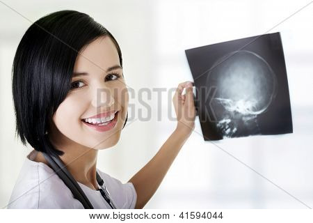 Female doctor or nurse looking at radiography photo at hospital