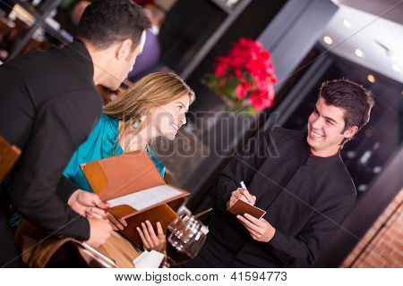 Waiter taking an order from a couple at the restaurant
