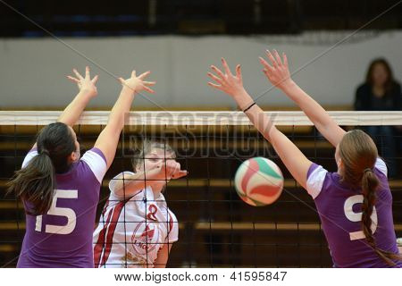KAPOSVAR, HUNGARY - JANUARY 27: Timea Kondor (in white) in action at the Hungarian I. League volleyball game Kaposvar (white) vs Ujpest (purple), January 27, 2013 in Kaposvar, Hungary.