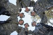 foto of huddle  - Low angle view of happy group of soldiers forming a huddle - JPG