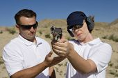 image of handgun  - Trainer helping young woman to aim with handgun at combat training - JPG