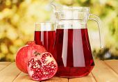 Full glass and jug of pomegranate juice and pomegranate on wooden table outdoor