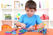 foto of molding clay  - Cute little boy moulds from plasticine on table - JPG