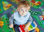 stock photo of diligent  - Little toddler boy playing with wooden music toy indoor - JPG