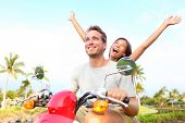 stock photo of couples  - Happy free freedom couple driving scooter excited on summer holidays vacation - JPG