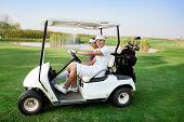 image of buggy  - Couple in  driving buggy on golf course - JPG