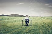 picture of nerd glasses  - Businessman sitting at a desk on a large field using a laptop - JPG