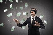 picture of blindfolded man  - Blindfolded businessman trying to catch a hundred - JPG