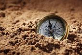 stock photo of compass  - Golden compass buried in the sand concept for lost or direction - JPG