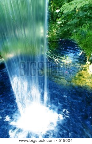 Behind A Waterfall In A Rain Forest With A Deep Blue Waterfall And A Green Backdrop