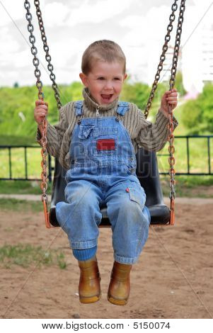 Boy Is Playng On The Swings
