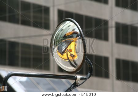 Convex Or Concave Mirror On A School Bus That Is Driving Through The City