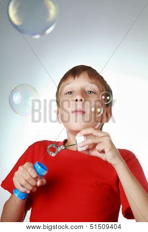 Beautiful blond boy in a bright red t-shirt blowing soap bubbles