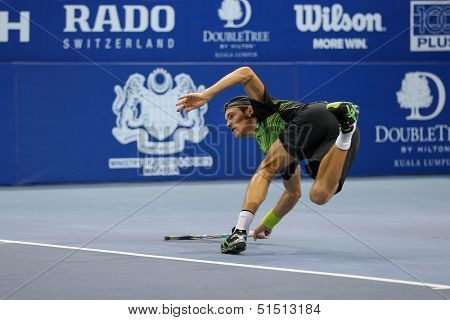 KUALA LUMPUR - SEPTEMBER 28: Joao Sousa plays a return to Jurgen Melzer in a semi-final match of the Malaysia Open 2013 tennis played at the Putra Stadium, Malaysia on September 28, 2013.