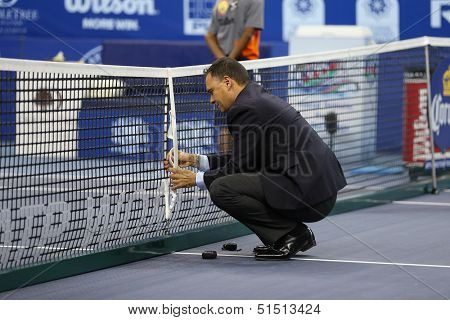 KUALA LUMPUR - SEPTEMBER 28: Umpire Mohamed Lahyani of Sweden measures the net height before the semi-final match of the Malaysia Open 2013 played at the Putra Stadium, Malaysia on September 28, 2013.