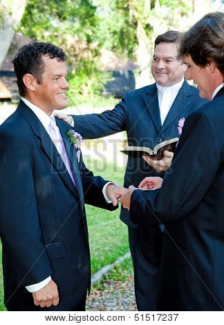 Groom slips a ring on his husband's finger during a gay marriage ceremony.