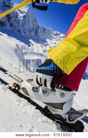 Ski, skier, skiing equipment - woman getting ready for skiing - fastening the boots