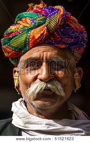 PUSHKAR, INDIA - DECEMBER 1: A Rajasthani man wearing traditional colorful turban posing after Pushkar Camel Fair on December 1, 2012 in Pushkar, Rajasthan, India.