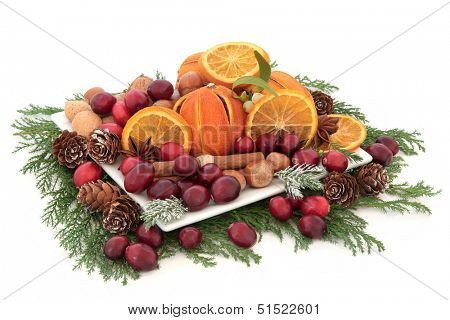 Christmas cranberry and dried orange fruit with nuts, spice and winter greenery over white background.