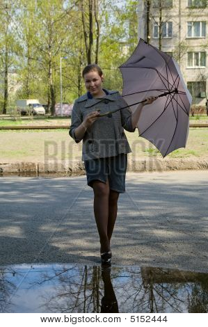 Young Woman Stays Before Puddle With Grey Umbrella