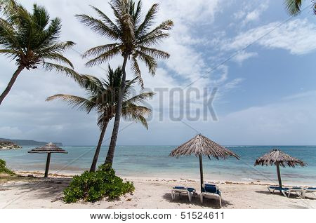 A Sunny Caribbean Beach With Sunloungers And Umbrellas