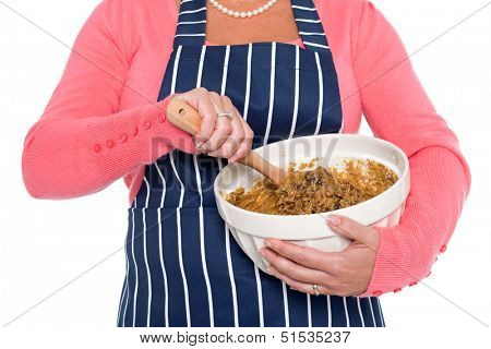Close up of a woman holding a bowl and mixing the ingredients for a cake, isolated on a white background.