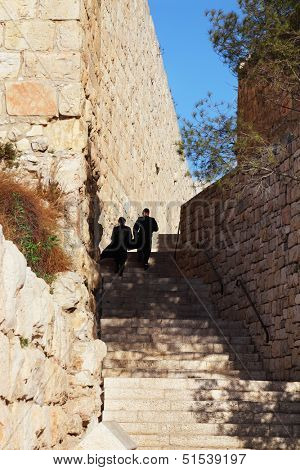 Two religious Jews lifted up the stone steps. Narrow lane near the walls of Jerusalem