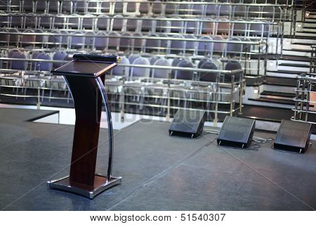 Document stand on black stage and rows of seats in empty concert hall.