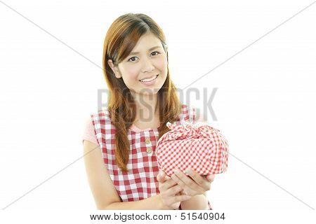 Young woman wearing kitchen apron with lunch box