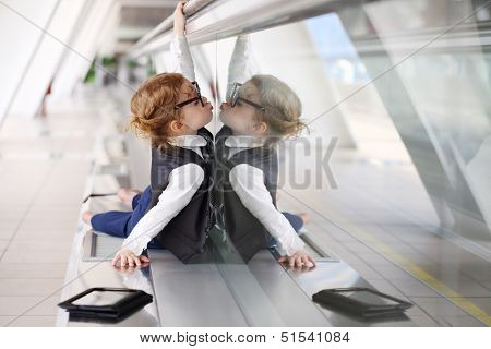 Little barefoot girl in tie lies on floor in gallery near glass wall and kisses her reflection.