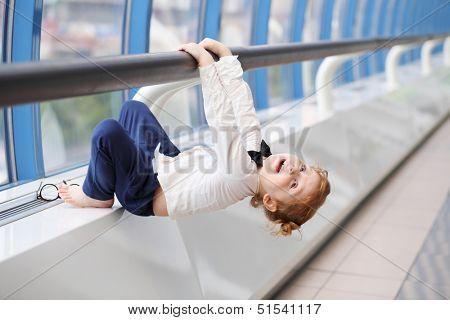 Little cute red hair girl in bow-tie hangs on handrail in gallery near window.