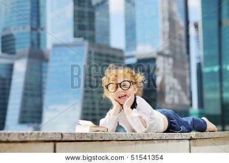 Little cute girl in glasses with book lies on border and laughs near skys?raper at sunny day.