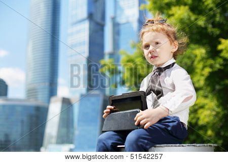 Little happy girl with tablet pc sits near tree near skys?rapers at sunny day.