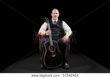 Musician In Vest And Tie Sitting In Red Velvet Chair Holding Guitar