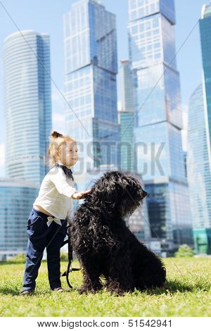 Little cute girl strokes big black dog near skys?rapers at sunny day.