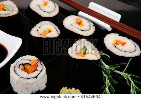 Maki Rolls and California rolls made of fresh raw Salmon, Tuna and Eel with Cream Cheese and Avocado . on black wooden plate . Maki Sushi and Nigiri
