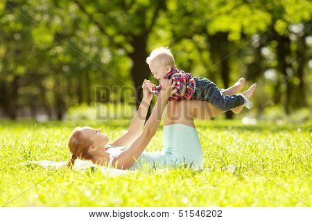 Cute little baby in summer  park with mother  on the grass. Sweet baby and mom  outdoors. Smiling emotional kid with mum on a walk. Smile of a child