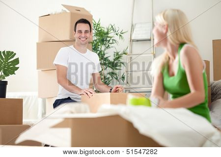 excited couple in new home unpacking boxes, concept moving into a new home.