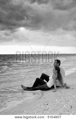 Pareja sentada en el agua en las playas y negro