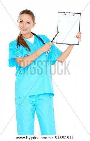 Smiling attractive young nurse or doctor in green scrubs holding up a blank clipboard in her hand and pointing towards it with a pen  isolated on white