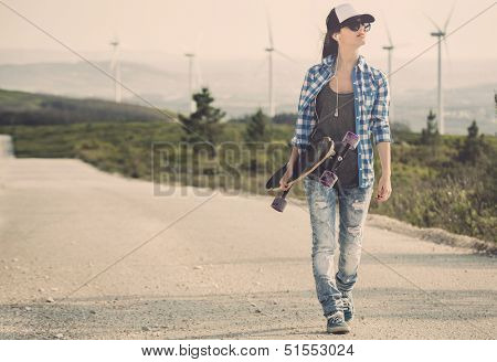 Beautiful Young woman walking and holding a skateboard