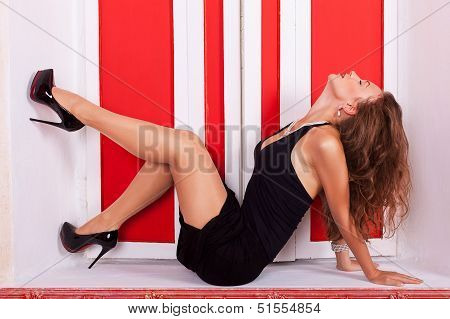 Sexy Woman In Evening Dress On A Sill In Front Of A Red Window Fashion Style