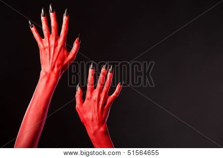 Red devil hands with black nails, Halloween theme, studio shot on black background