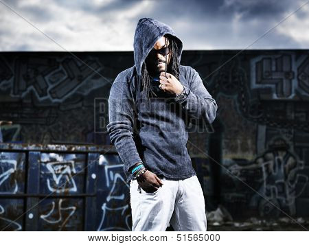 man in hoodie in front of graffiti